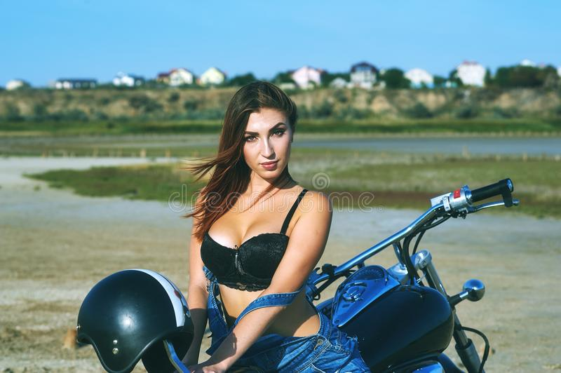 Young woman on a motorcycle on a summer day royalty free stock photo