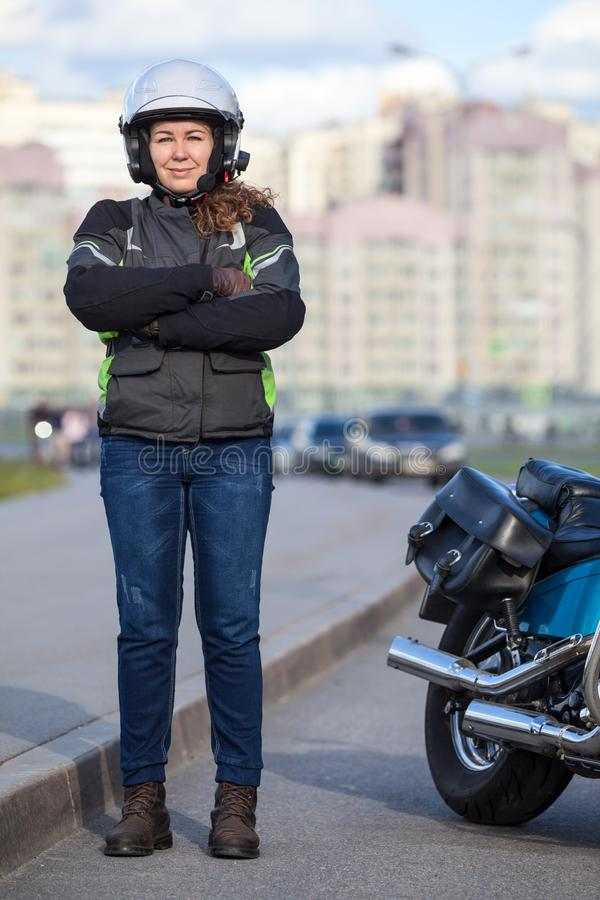 Young woman motorcyclist standing roadside near her motorcycle, full length portrait with cross arms on breast stock photography