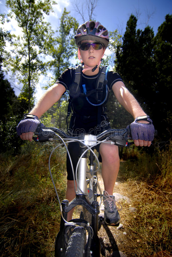 Young Woman Mountain Biking Royalty Free Stock Images