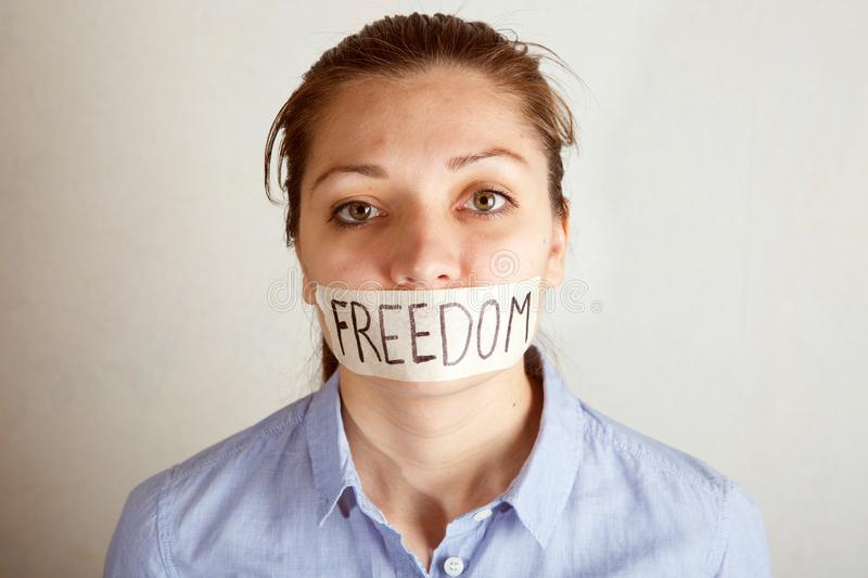 Young woman with mouth covered with tape. royalty free stock images