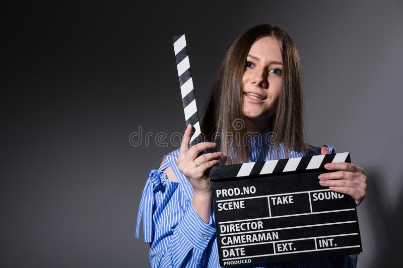 Young woman with movie clapper. Assistant director girl with long hair and striped shirt on a gray background stock image