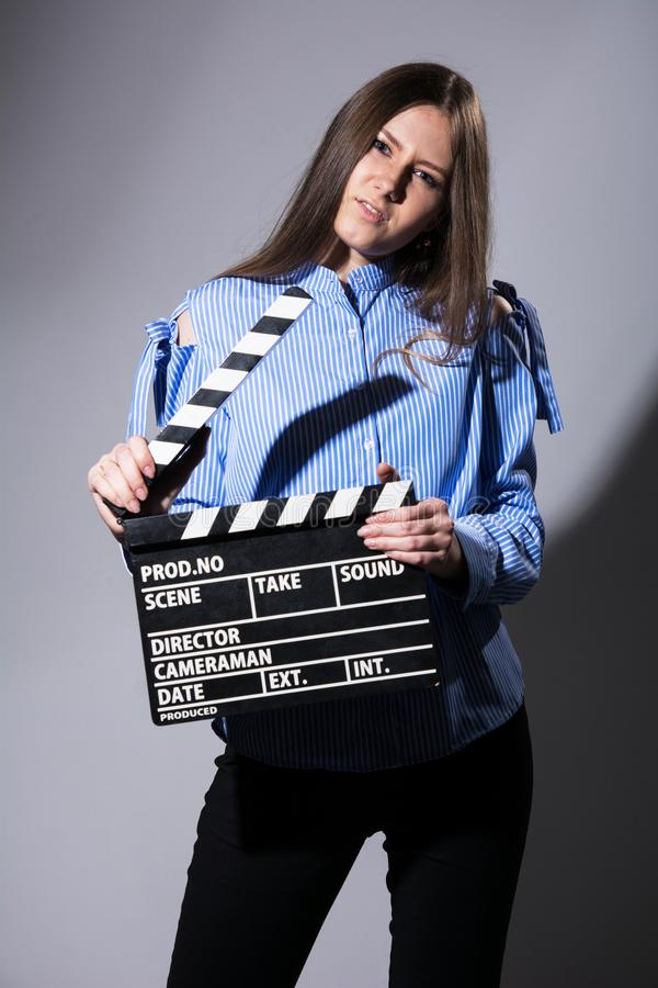 Young woman with a movie cracker. Assistant director girl with long hair and striped shirt on a gray background royalty free stock image