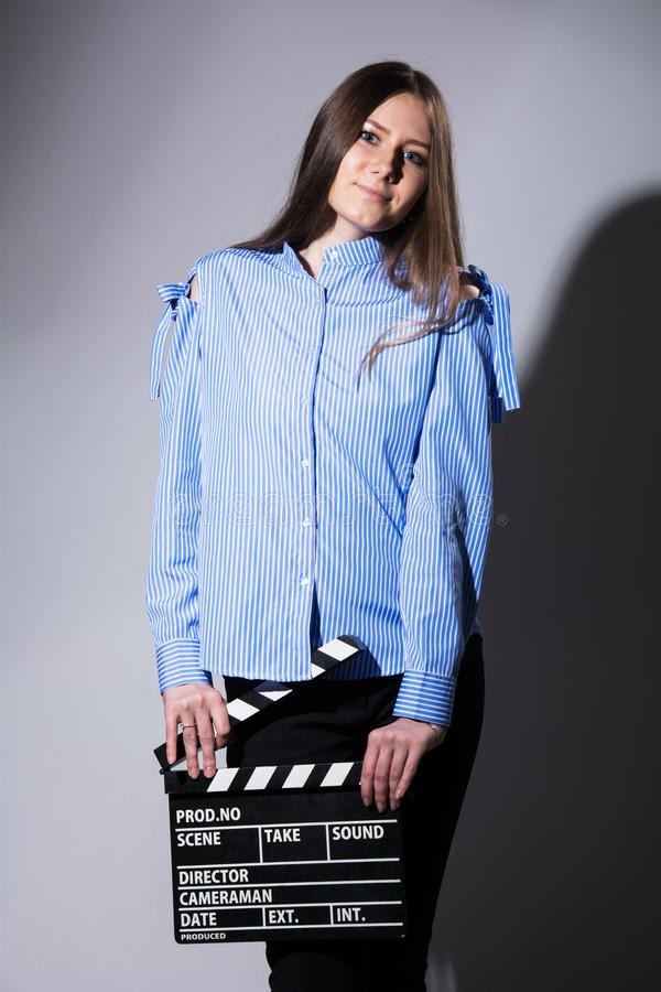 Young woman with a movie cracker. Assistant director girl with long hair and striped shirt on a gray background royalty free stock images