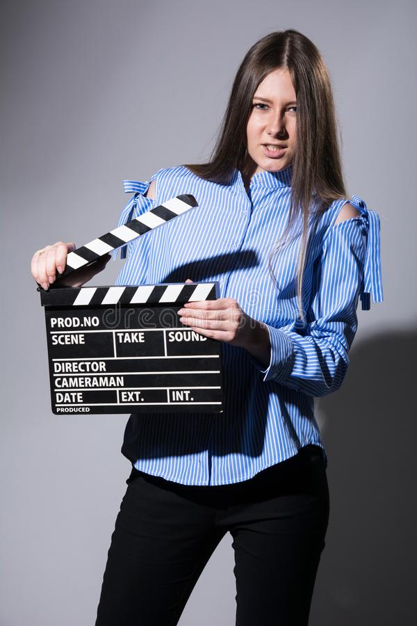 Young woman with a movie cracker. Assistant director girl with long hair and striped shirt on a gray background stock photo