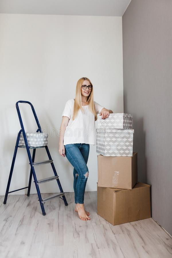 Young woman moving in her new house and doing a home makeover, she is standing near many cardboard boxes around stock photography