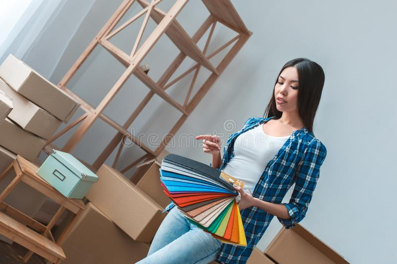 Young woman moving to a new place standing holding palette planning design stock image