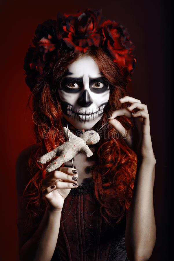 Young woman with muertos makeup (sugar skull) piercing voodoo doll. Young woman with muertos makeup (sugar skull) piercing a voodoo doll royalty free stock photography