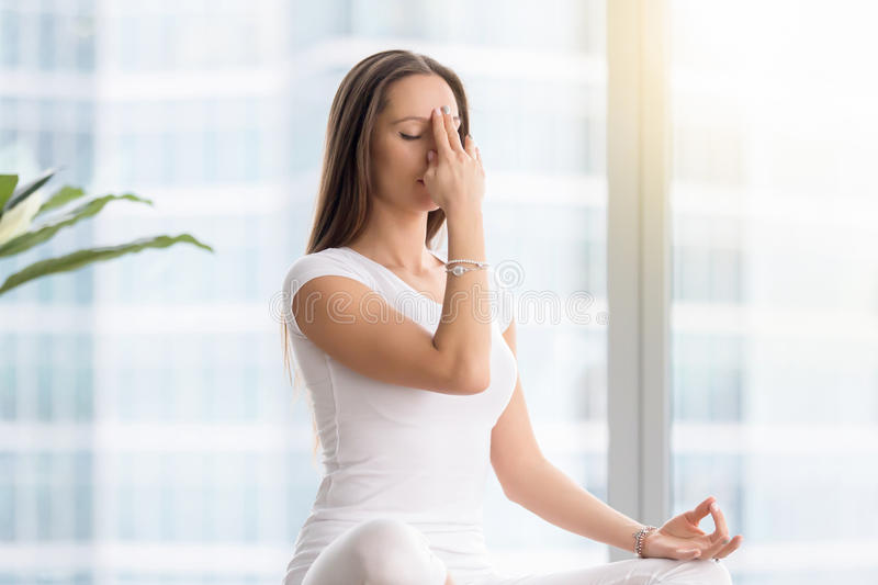 Young woman in nadi shodhana pranayama against floor window. Young attractive woman practicing yoga exercise, sitting in Sukhasana pose, performing Alternate stock photo