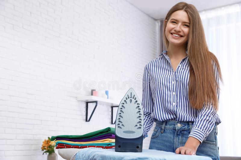 Young woman near board with iron and clothes at home. Space for text royalty free stock photography