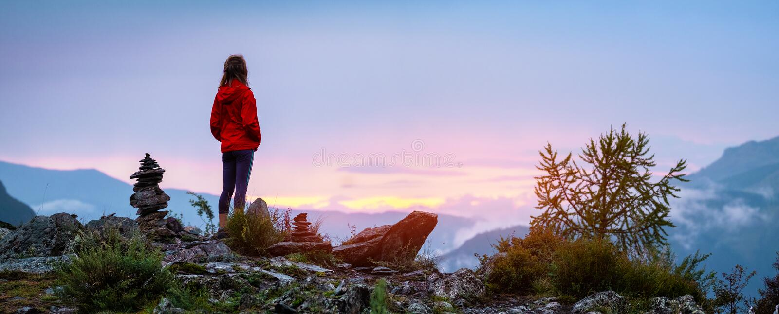 Young woman near cairns. Panorama with lady hiker standing on top of the mountain among stacked stones and enjoying sunset over the valley. Altai, Russia stock image