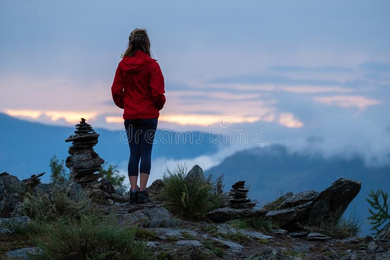 Young woman near cairns. Young woman in red stands near the cairns and looks into the valley at sunset. Altai Republic, Russia. Image has some noise stock photography