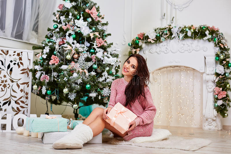 Young woman near a Christmas tree holding gift box stock images