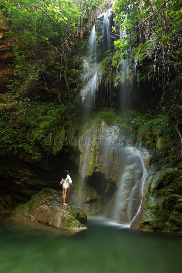 Young woman near waterfall. Young woman with hands up near waterfall royalty free stock image