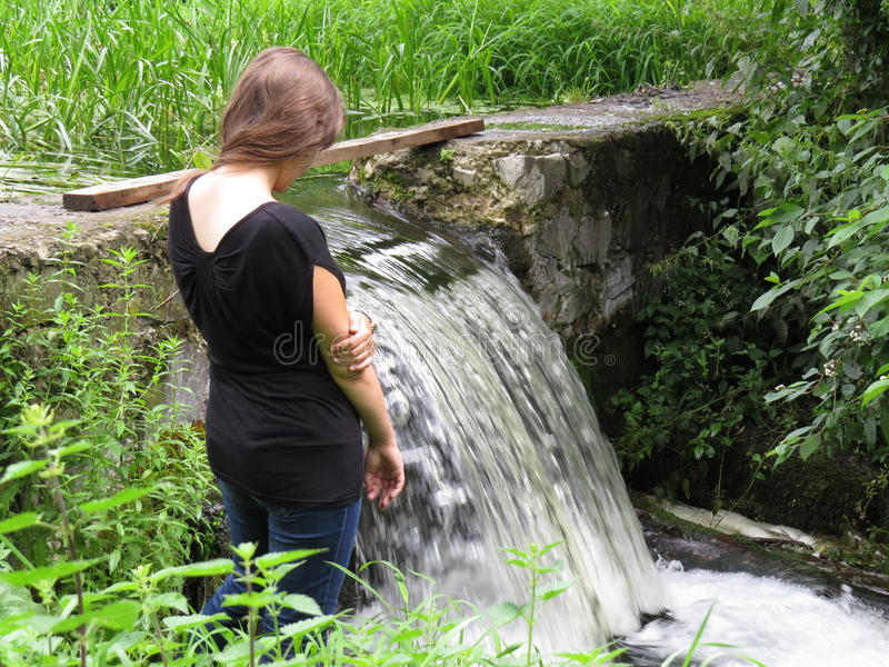 Young woman near a waterfall. Young woman near a small artificial waterfall royalty free stock photo