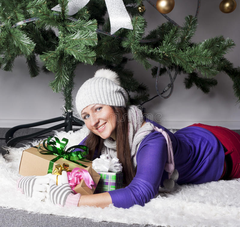 Young woman near xmas tree with presents stock photography
