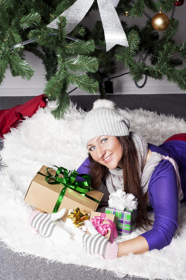 Young woman near xmas tree with presents royalty free stock photos
