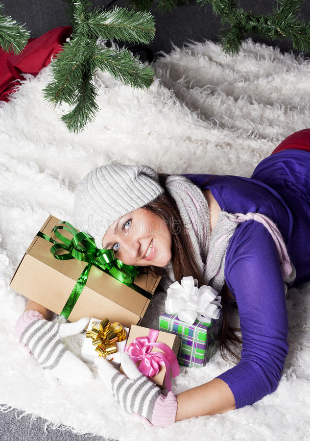 Young woman near xmas tree with presents royalty free stock image