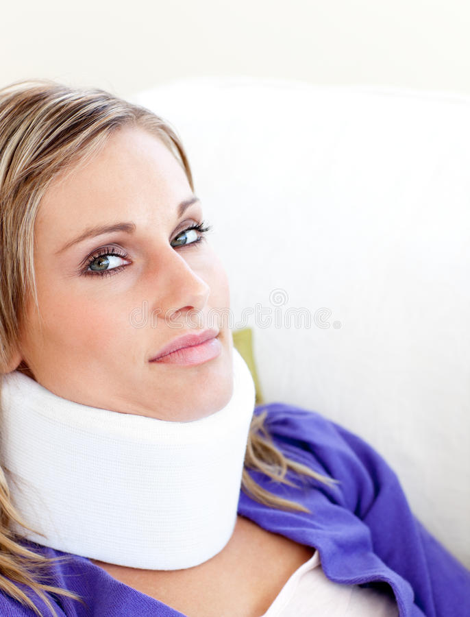 Young woman with a neck brace. Looking at the camera against white background royalty free stock photography