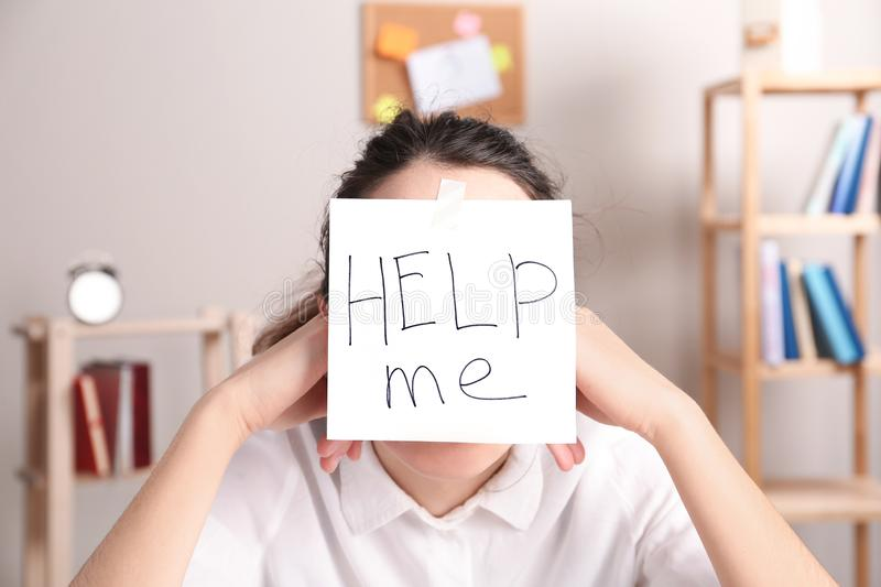 Young woman with note HELP ME on forehead royalty free stock image