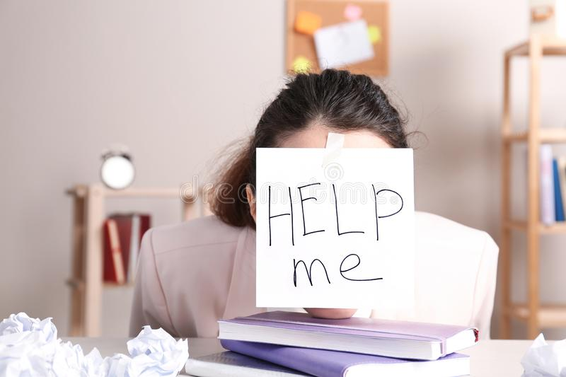Young woman with note HELP ME on forehead stock image