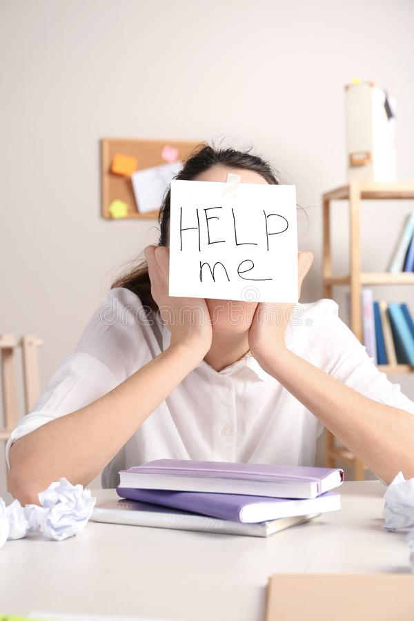 Young woman with note HELP ME on forehead royalty free stock photos