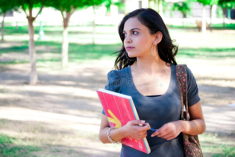 Young woman with notebook. Young woman with a notebook and backpack at the park stock photos