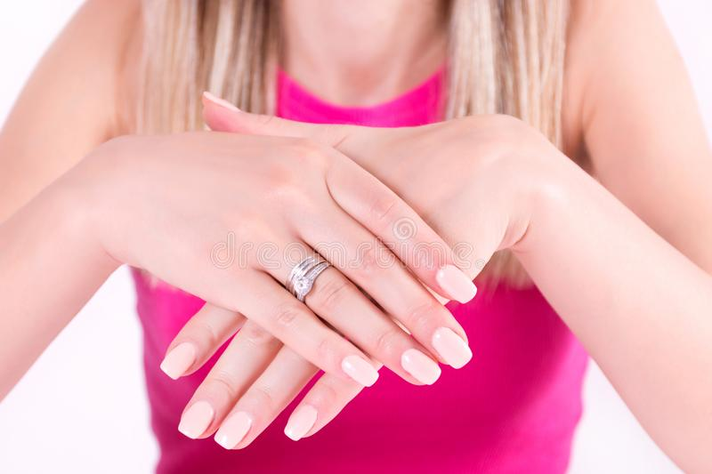 Young woman with nude color manicure nails polish gel and diamonds ring on finger royalty free stock photo