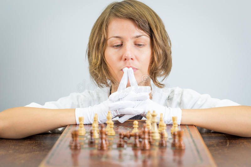 Young woman nurse doctor playing chess checkmate thinking game pieces. Young beautiful pretty woman nurse doctor female playing chess, white robe gloves moving royalty free stock photography