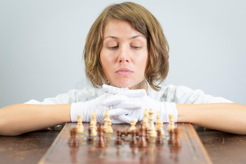 Young woman nurse doctor playing chess checkmate thinking game pieces. Young beautiful pretty woman nurse doctor female playing chess, white robe gloves moving stock images