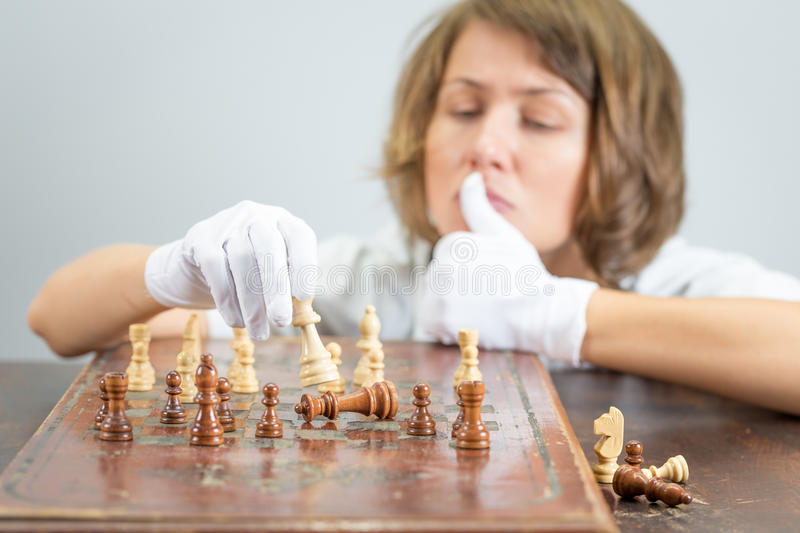 Young woman nurse doctor playing chess checkmate thinking game pieces. Young beautiful pretty woman nurse doctor female playing chess, white robe gloves moving stock photo