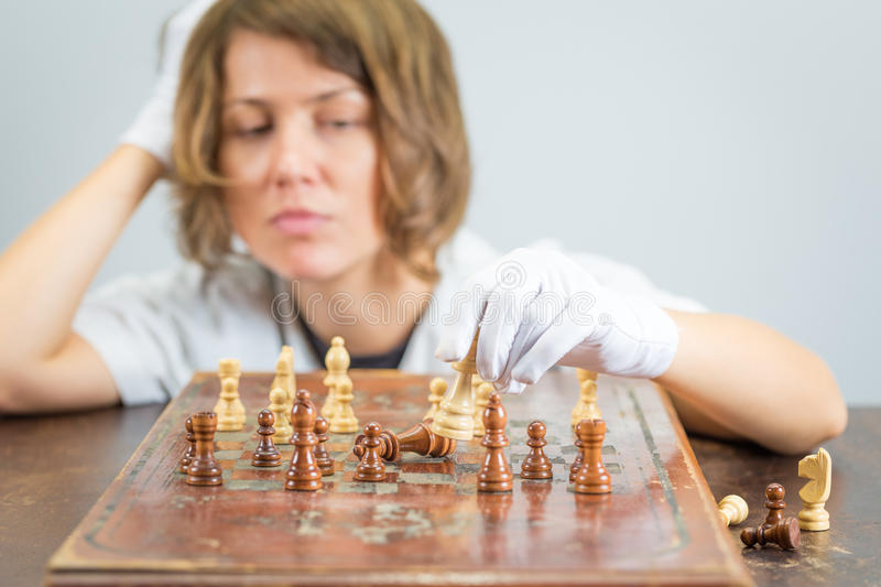 Young woman nurse doctor playing chess checkmate thinking game pieces. Young beautiful pretty woman nurse doctor female playing chess, white robe gloves moving royalty free stock image