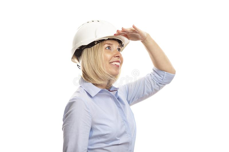 Young woman in office clothes and a construction helmet looks into the distance. Close-up. White background royalty free stock image