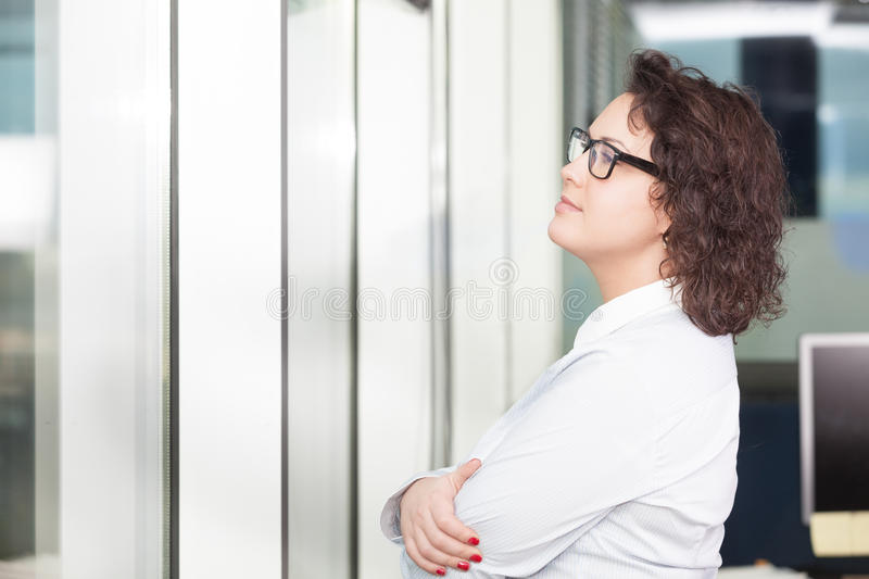 Young woman at the office looking at the window. Young relaxed woman at the office looking at the window royalty free stock images