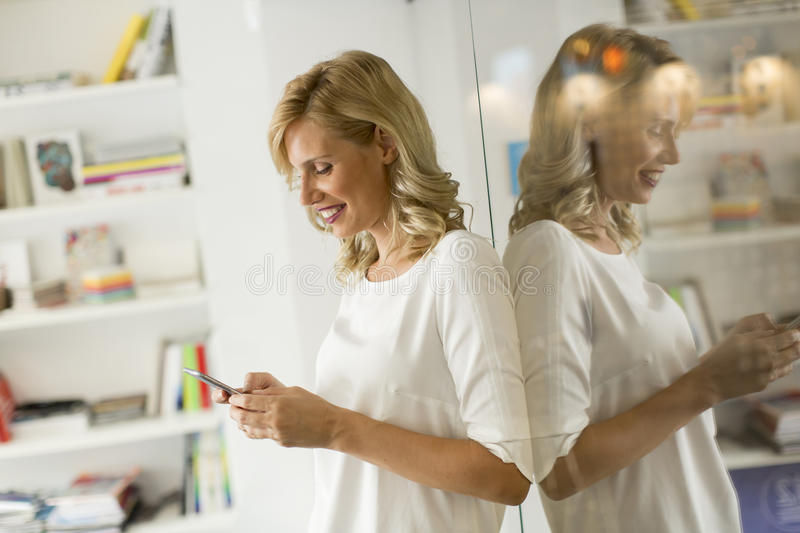 Young woman in the office. Young woman with a phone in the office royalty free stock photo