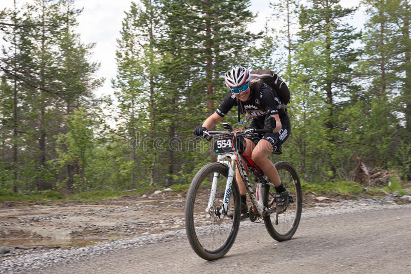 Young woman offroad cycling. Girl bicycle offroad race in Finnmark on dirt road stock photos