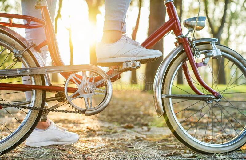 Young woman on old style italian bicycle with back light - Close up of girl feet riding vintage bike in park outdoor for fall time royalty free stock photo