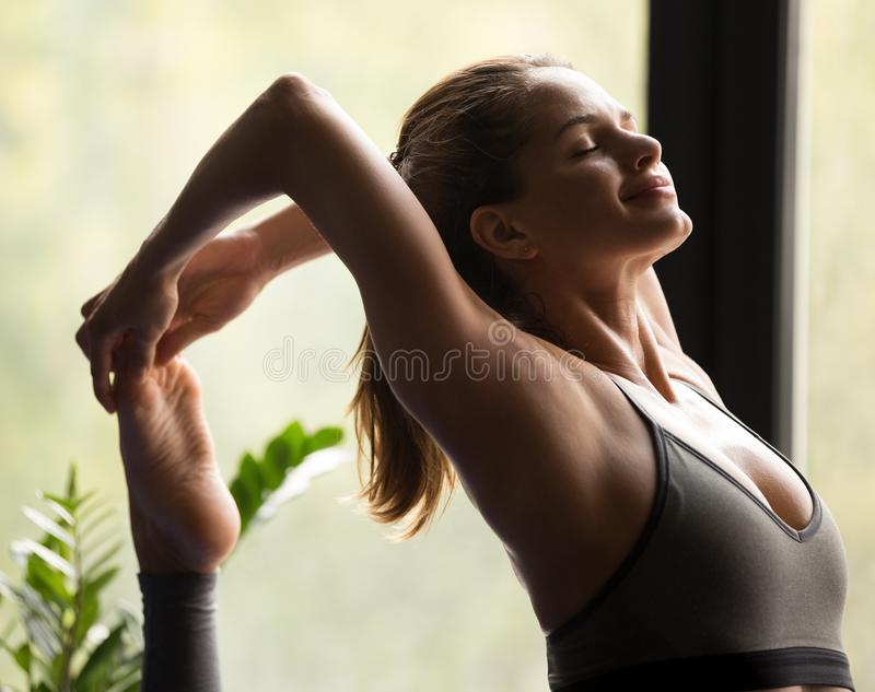 Young woman in One Legged King Pigeon pose, close up stock image