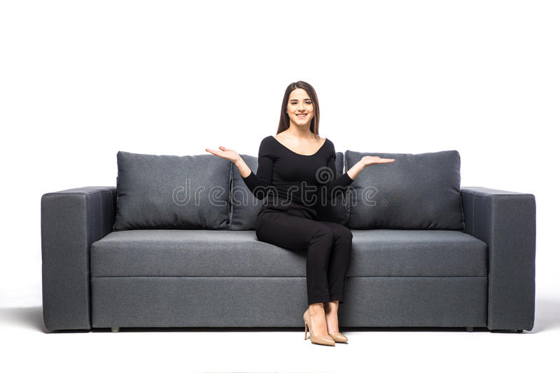 Young woman with open palm sitting on sofa on white background. Woman with open palm sitting on sofa on white background royalty free stock images