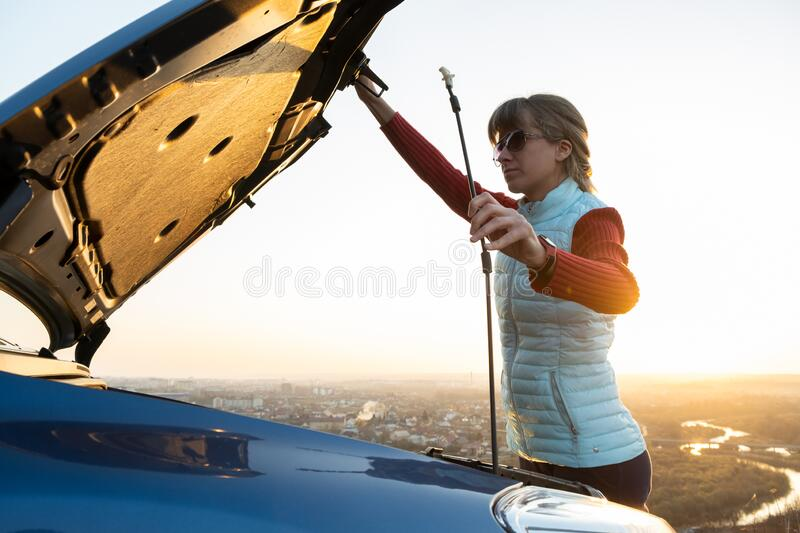 Young woman opening bonnet of broken down car having trouble with her vehicle. Female driver near auto with popped up hood.  royalty free stock photo