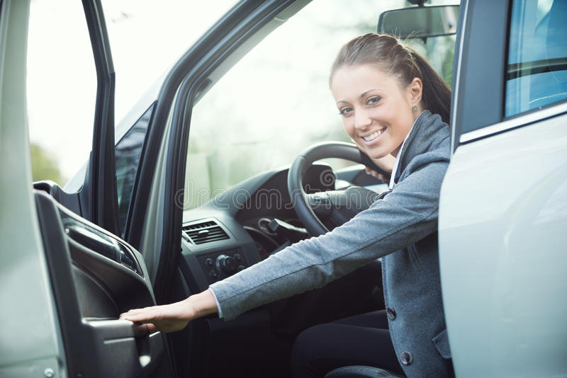 Young woman opening car door stock image