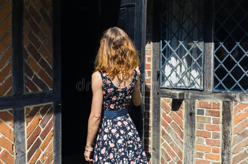 Young woman opening door and entering old building royalty free stock photos