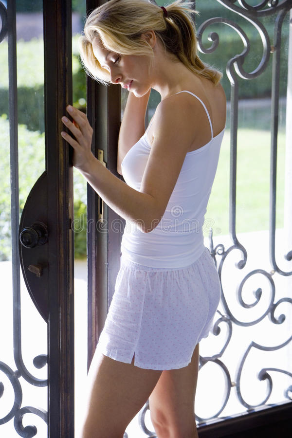 Young woman opening gate, side view stock photos