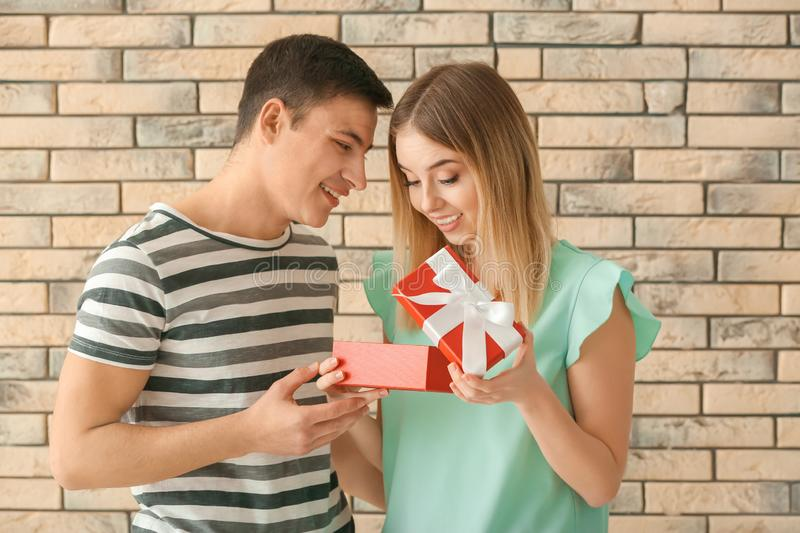 Young woman opening gift box from her boyfriend near brick wall. Young women opening gift box from her boyfriend near brick wall royalty free stock image