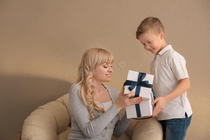 Young woman opening gift from her son on color background. Mother's day celebration stock image