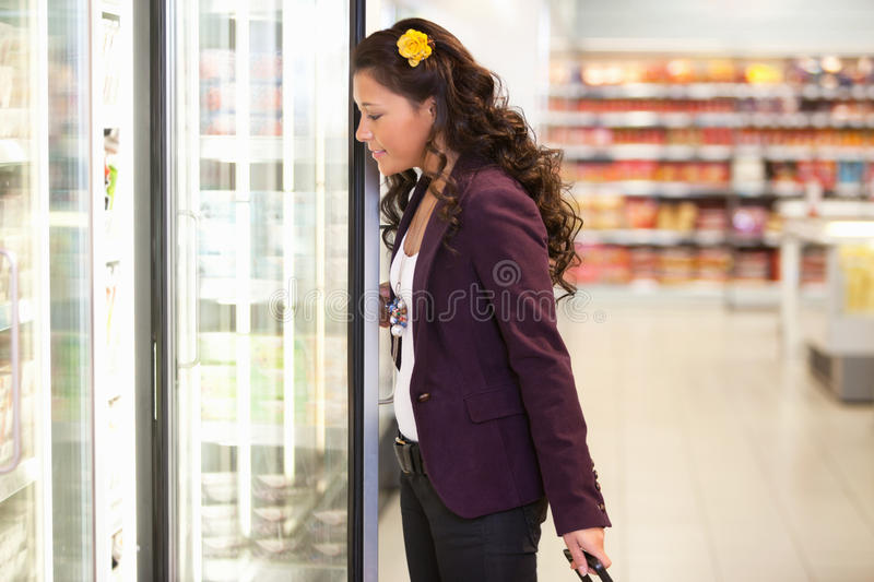 Young woman opening refrigerator stock images