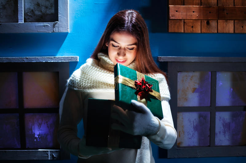 Young woman opens her gift Christmas in a magical house royalty free stock photos