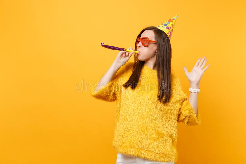 Young woman in orange funny eyeglasses birthday party hat with playing pipe looking aside celebrating isolated on bright. Yellow background. People sincere stock photography