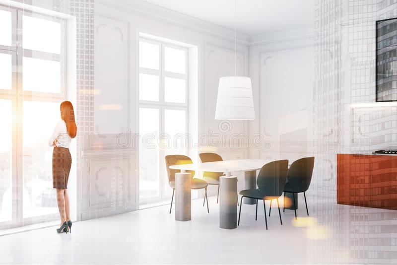 Young woman in orange kitchen with table. Rear view of young woman in business suit standing in luxury kitchen interior with white walls, French windows, massive stock photos
