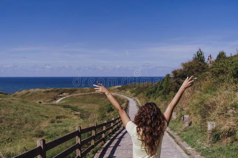Young woman outdoors Enjoying a sunny and windy day. Fun, summertime and holidays concept. Back view stock photos