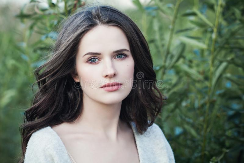 Young woman outdoors on green spring leaves background. Beauty girl face closeup. Portrait royalty free stock photo